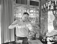 Frank Sinatra pouring a drink at his home bar, in 1965