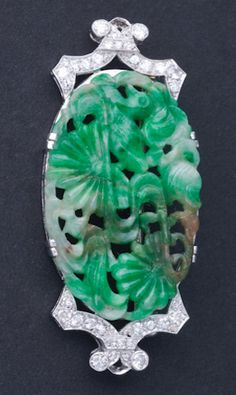 Art Deco jade and diamond panel brooch in pt. Mine and transitional-cut diamonds, approx. .50 ct TW. Pierced and carved panel depicts duck on pond with lilies.