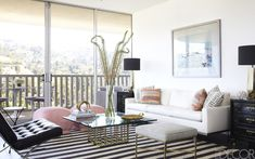 In the living room of television producer Ellen Rakieten's Los Angeles apartment, which was designed by Anne Coyle, a Louis XV–style desk by Baker is paired with a side chair by Jonathan Adler. The 1940s chandelier is Italian, and the mirrored walls and concrete flooring are original to the apartment. Tour the rest of the home.