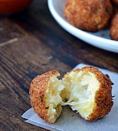 Rice Balls w/ Marinara Sauce. 2 cups cooked white rice,½ cup grated Parmesan,3 eggs,8 small cubes fresh mozzarella, 1 cup Italian-style breadcrumbs, Oil, 1 cup marinara sauce. Roll into balls fry.