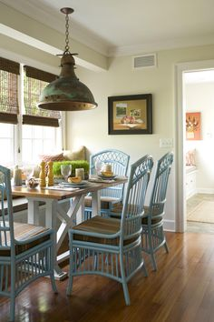 Built-in window seats and cozy benches are attractive solutions for creating compact seating space in kitchens or other high-traffic rooms. In this space, the windows work with the cheerful blue chairs to open up the kitchen and make the most of this small breakfast nook.
