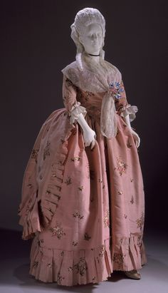Robe à la Polonaise, England, c. 1770-1780. Brocaded pink silk taffeta with floral sprays in coloured silk. The pink color of this dress and its petticoat is typical of the late eighteenth century. The gown features a skirt shorter than its petticoat; buttons and braid hold the overskirt in draped swags at the back.