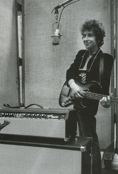 Bob Dylan at the studio microphone with guitar, standing behind the stack. - http://www.pinterest.com/claxtonw/music-studio-stuff/ - A fascinating smile on the young musician in this vintage photograph taken in the music studio, which has become a MOST POPULAR RE-PIN https://www.pinterest.com/DianaDeeOsborne/ddo-most-popular-re-pins/ - for lovers of more modern music history.