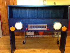 Car headboard. I took an old bookshelf headboard and painted it metallic blue. The headlights are tap lights, so they turn on as a reading lamp. The grill is a grate for heating ducts painted chrome. Reflectors were used for the turn signals.
