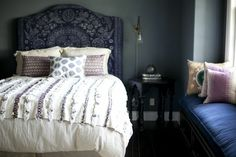 Designer Amber Lewis chose a moody blue spectrum paired with block-print pillows and a Moroccan wedding blanket for this bohemian-inspired bedroom.