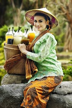 Traditional Jamu seller typically wearing kebaya with weaved ratan basket containing jamu mixtures in glass bottles.