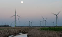 The full moon shines behind a wind park near Norden, Germany.