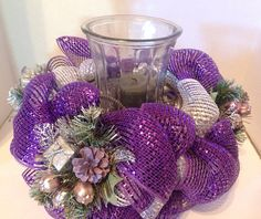This is a beautiful purple and silver Christmas centerpiece. It is made with a wire basket that can hold a large candle holder or flower vase. It is made with metallic deco mesh with matching Christmas decor added. It measures approximately 8 inches tall and 13 inches wide. The opening in the basket is 5 inches. For the picture I used a hurricane vase. The hurricane vase and candle is NOT included in the listing