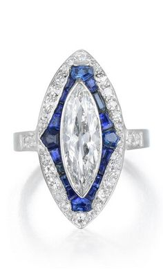 An Art Deco Sapphire and Diamond Ring. Featuring an elongated marquise diamond, surrounded by calibré-cut blue sapphires and old single-cut diamonds, all set in a 14K white gold mounting. #ArtDeco