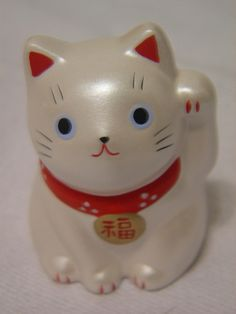 To some Westerners it may seem as if the maneki-neko is waving rather than beckoning.This is due to the difference in gestures and body language recognized by some Westerners and the Japanese. The Japanese beckoning gesture is made by holding up the hand, palm out, and repeatedly folding the fingers down and back up, thus the cat's appearance.