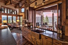 Rustic ranch house in Colorado opens to the mountains This modern rustic retreat was designed by Terra Firma Custom Homes in collaboration with JJ Interiors, located in the mountains of Aspen Springs, Colorado. Kitchen Window Bar, Kitchen Cabinet Layout, Farmhouse Kitchen Cabinets, Rustic Kitchen, Kitchen Ideas, Kitchen Floor, Rustic Farmhouse, Kitchen Windows, Smart Kitchen