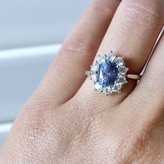This ring features an ethically sourced, unheated, untreated, 2.24ct, oval blue sapphire from Sri Lanka. It is set with 10 excellent cut round brilliant cut diamonds surrounding it, in a Princess Diana inspired Sapphire Engagement ring. The diamonds weigh a total of 1ct and are F/G colour, VS/SI quality, Very Good Cut. This ring is 19K white gold and is currently a size 6. Sapphire Diamond Rings, Sapphire Engagement Rings, Princess Diana Engagement Ring, Princess Diana Ring, Saphire Ring, Sapphire Wedding Rings, Dream Engagement Rings, Engagement Ring Styles, Coloured Engagement Rings