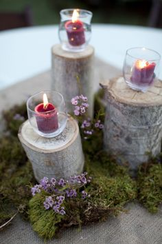 centerpieces of log sections surrounded by moss, with flowers interspersed, and votive candles in glass holders