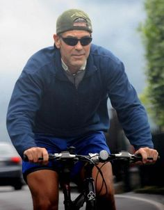 George Clooney rides a bike.