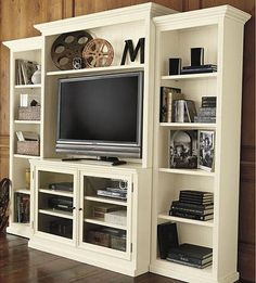 Metal film reels are a great decoration for an entertainment center. a stack of black books also adds a nice contrast to a white entertainment center. Media Furniture, Home Office Furniture, Furniture Ideas, Entertainment Wall, Black And White Living Room, Black White, Living Room Photos, Living Rooms, Ideas