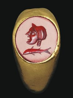 A ROMAN GOLD AND CARNELIAN FINGER RING   CIRCA 1ST CENTURY B.C.   The hollow hoop rounded on the exterior, flat on the interior, expanding to the shoulders, the oval bezel set with a flat stone engraved with a theater mask in profile to the left, a fish in the field below