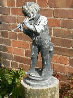 """A vintage lead figure of a boy playing a pipe on an associated granite column. The lead boy has an attractive weathered grey patination and is in good condition for it's age. It was probably made by the long established family lead-making business trading as H. Crowther, Chiswick, London.  Early 20th Century  53"""" high overall  £795 for the lead figure £180 for the granite column"""