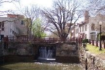 C & O Canal - Upstream view of Lock 4 gates with water spilling through, flanked on each side by Georgetown rowhouses.