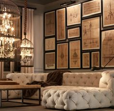 living room - gallery wall with caged chandeliers and a tufted sofa....warm and inviting