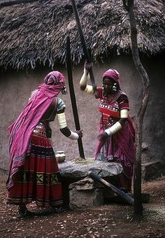 INDIA: Two woman in pink sarees grinding grains. Banjara, Andhra Pradesh