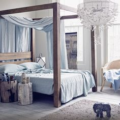 Neutral bedroom with wooden four-poster bed and blue accents