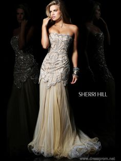This sophisticated evening dress breathes class, glamour and elegance. Sherri Hill 21096 is a fit and flare nude design featuring a strapless bodice embellished with beaded swirls that stretch onto the asymmetrical dropped waist which ends with scallops along its trim. Yards and yards of sheer material create a flared skirt that sweeps the floor in a dazzling way. Purchase this refined prom gown 2013 in Ivory/Silver. Look your best by wearing Silver toned jewelry and chic high heels.