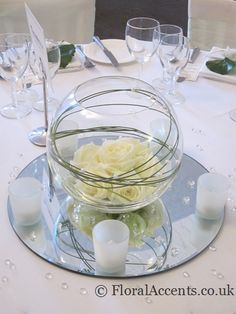 Wedding flowers - glass fishbowl table centres with a dome of cream roses - by Floral Accents