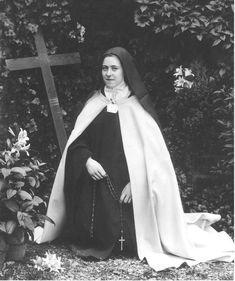 sainte-Therese-de-Lisieux kneeling near the Marian shrine in the garden