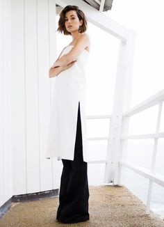 The Chronicles of Her wears an elegant and minimalist white tunic with a side slit and black wide-leg pants
