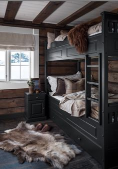 Rustic styled guest bedroom with black bunk beds. Hewn walls and fur pelts. Black Bunk Beds, Bunk Beds With Stairs, Cabin Bunk Beds, Rustic Bunk Beds, Cabin Bedrooms, Loft Stairs, Cozy Cabin, Cozy House, Cabin Homes