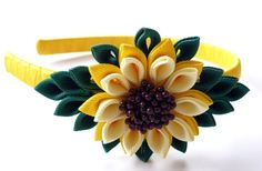 A flower is made in the technique of tsumami kanzashi.  Plastic headband is weaved with satin ribbon.  Flowers are made from grosgrain ribbons. At your