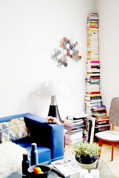 Stack of books and blue sofa in living room.