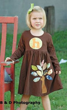 A gorgeous whimsical applique dress featuring leaves of several designer fabrics sewn over the corduroy tree trunk. Shades of green, blue,