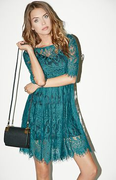 Fit and flare dress featuring a sheer lace overlay with eyelash edges, ribbon band around waist, elbow-length sleeves, removable slip lining, and an exposed back zipper with hook and eye closure. By BB Dakota.