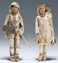 Wood-carved Eskimo-Inuit Dolls wearing traditional seal hide clothing.