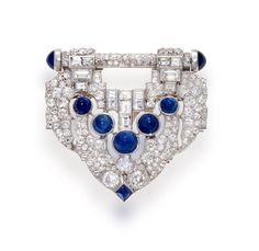 An art deco sapphire and diamond clip-brooch, J.E. Caldwell, circa 1925  the shield-shaped panel set throughout with old European-cut diamonds and further accentuated by baguette-cut diamonds and sugar loaf sapphires; signed JEC & Co., estimated total diamond weight: 9.00 carats; mounted in platinum; length: 1 3/4in.