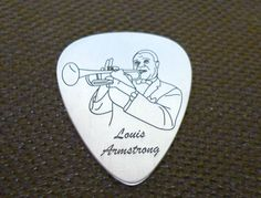 This awesome silver pick is inspired by Louis Armstrong (1901-1971), one of the most influential figures in jazz  Made of rhodium plated sterling silver 925  Dimensions: 30mm height, 0.6mm thickness  Our designs of the silver picks are based on famous pictures related to music history  Manufacturing process includes treatment by hand and laser engr