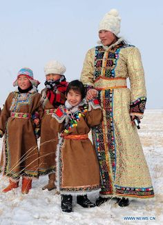 A woman and her children in traditional holiday attire of the Mongolian ethnic group watch camels racing at an ice and snow carnival in West...