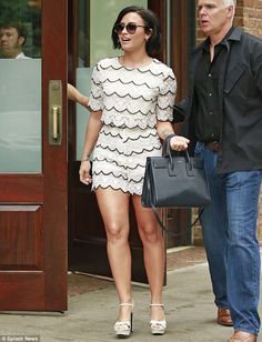 Beaming: Accompanied by her entourage, the 22-year-old looked nothing short of glamorous in her style choice as she meandered through the streets, smiling widely