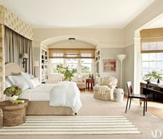 In the master suite, a bed upholstered in a Loro Piana cotton is paired with a valance and curtains of a Schumacher print