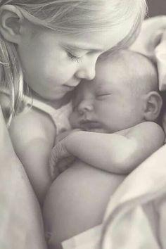 Big sister cuddling new born
