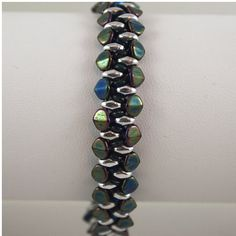 This bracelet has been hand bead woven using iridescent green pinch beads, silver super duo beads and emerald o beads. The bracelet is 3/8