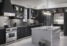 This black kitchen incorporates glass-front cabinets, marble countertops and three sinks, including a prep sink for entertainment. U Shaped Kitchen, Kitchen And Bath, Black Kitchens, Home Kitchens, Glass Front Cabinets, Bar Faucets, Kitchen Colour Schemes, Kitchen Floor Plans, Floor Trim