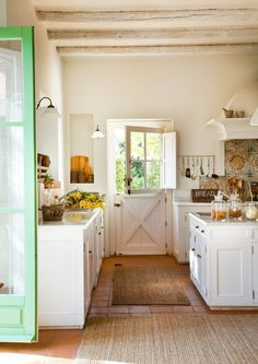 White with pops of color. Wood floors. Simple lighting. Rustic look. Burlap rugs. Aged beams. French barn door with window.  #kitchen #rustic #barndoor