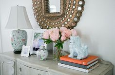 Love how this is styled - peacock mirror, vintage lamp, & a foo dog!