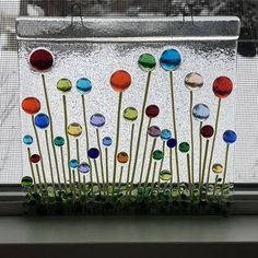 The colorful round flowers of this charming fused glass suncatcher bring the summer into your house all year round. This suncatcher makes a beautiful gift for any occasion. The item was tack fused in my kiln at around 1300F so that the flowers are raised and add structure and