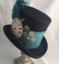 Steampunk Bell Top/Mad Hatter Hat   Steampunk top hat, black wool felt with turquoise wide band going around the crown, big clock face with minute and hour hands, beautiful turquoise ostrich plume and small clock parts and gears. This hat frame is a very high quality felt hat with lining. Note: You must measure your head. DO NOT GUESS. I do not take returns if you order the wrong size. Sizing: Choose your size in the drop down menu when you add to cart.  Medium - 7-7 1/8 or 22 - 22 ...