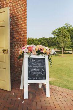 Chalkboard welcome signage with a lovely arrangement on top #wedding #gardenparty #diywedding #weddingdecor #gardenwedding