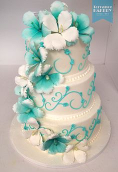 Teal-and-white wedding cake decorated with a big and beautiful cascade of gumpaste flowers!