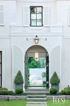 The large scale of the home's elegant arched entryway provides a dramatic first impression of luxury and space. The view through the glass doors to the backyard fountain is one of the owners' favorites.